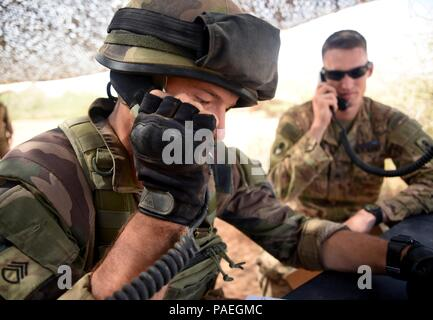 A French Army Soldier simulates calling in suspicious activity March 31, 2016, during the patrolling portion of the EIB course at Camp Lemonnier, Djibouti. The patrolling day included the most diverse categories of the course such as face paint, radio calls, hand signals and gas mask drills. (U.S. Air Force photo by Staff Sgt. Kate Thornton) - Stock Photo