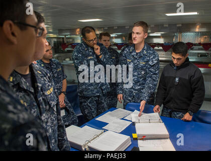 160322-N-WY954-069SAN DIEGO (March 22, 2016) – Ensign James M. Snead (second from right), from Long Island, New York, and Electronics Technician 3rd Class Kevin M. Delrio (right), from Visalia, California, instruct Basic Division Officer Course students on proper spot-check procedures in the USS Makin Island (LHD 8) wardroom. Students toured the ship and received hands-on training on 3M, zone inspection, tag-out, and hazardous materials programs to better prepare them for their first division officer tours.  Makin Island is home-ported in San Diego. (U.S. Navy photo by Mass Communication Speci - Stock Photo