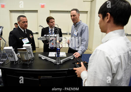 NATIONAL HARBOR, Md. (May. 16, 2016) Mike Osborn, second from right, program manager, Naval Research Laboratory, explains the Meso-scale Robotic Locomotion Initiative (MeRLIn) to Rear Adm. Mat Winter, chief of naval research, during a visit to the Office of Naval Research exhibit at the 2016 Sea-Air-Space Exposition. Sea-Air-Space is hosted by the Navy League of the United States with the goal of bringing together leaders from defense organizations, both government and private industry, to learn about and view the most up-to-date information and technology related to maritime policy. - Stock Photo