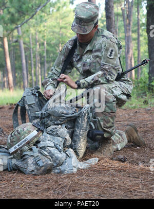 Staff Sgt. Gretchen Martinez from the Fires Center of Excellence gets her equipement ready to go through the react to direct/indirect fire lanes during the TRADOC Best Warrior Competition, Fort Gordon, Georgia, July 18, 2018. The Best Warrior Competition recognizes TRADOC NCOs and Soldiers who demonstrate commitment to the Army Values, embody the Warrior Ethos, and represent the force of the future by testing them with physical fitness assessments, written exams, urban warfare simulations, and other warrior tasks and battle drills. (U.S. Army photo by Pfc. Caeli Morris) - Stock Photo