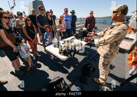 SEATTLE, Wash. (July 30, 2015) Damage Controlman 1st Class Benrichard Victorino, a Los Angeles native assigned to USS Gridley (DDG 101), presents equipment used in anti-terrorism force protection during ship tours on the Arleigh Burke-class guided missile destroyer for Seafair Fleet Week. Seafair Fleet Week is an annual celebration of the sea services wherein Sailors, Marines and Coast Guardsmen from visiting U.S. Navy and Coast Guard ships and ships from Canada make the city a port of call. - Stock Photo