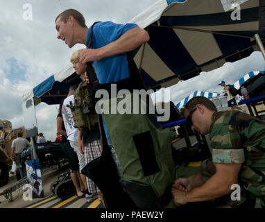 Petty Officer 3rd Class Steve Bechtel, explosive ordnance disposal technician, assigned to Explosive Ordnance Disposal Mobile Unit 2, helps a guest into an EOD bomb suite during the 52nd Naval Air Station Oceana Air Show. The air show featured Navy Expeditionary Combat Command capabilities from riverine, maritime expeditionary security, EOD, and Navy divers. - Stock Photo