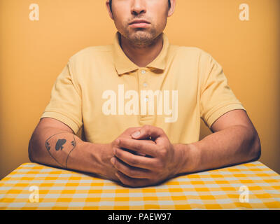 Young man against yellow backdrop is contemplating - Stock Photo
