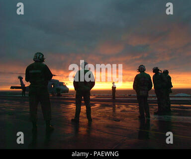 Deck personnel on board the U.S. Navy's oldest nuclear powered aircraft carrier USS Enterprise (CVN 65), secure a SH-60H 'Seahawk' assigned   to Helicopter        Anti-Submarine Squadron One Five (HS-15) at sunset, April 26, 1996.  Enterprise and Carrier Air Wing One Seven (CVW 17) are participating in Combined Joint Fleet Exercise '96, as part of a multinational force of over 50,000 Soldiers, Sailors, Airman and Marines from Canada, Britain and the United States. U.S. Navy - Stock Photo
