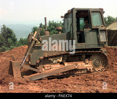 Albania (June 16, 1999) -- Equipment Operator Constructionman Dan Lasich from Rosenberg, OR, flattens out ground at Camp Wedge, Naval Mobile Construction Battalion FOUR (NMCB FOUR). Forward Operating Base in Albania.  NMCB Four will be doing 25 miles of roadwork near Kukes, Albania in support of Operation Shining Hope.  Operation Shining Hope is the multinational NATO and U.S. operation bringing food and shelter to thousands of Kosovo refugees.  U.S. Navy - Stock Photo