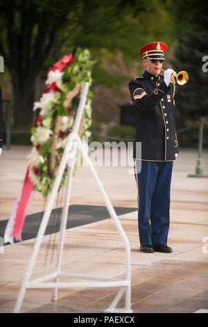"A bugler from The U.S. Army Band ""Pershing's Own"" plays Taps during a wreath-laying ceremony with Minister Predrag Matic, not pictured, Republic of Croatia Minister of Veterans Affairs, at the Tomb of the Unknown Soldier in Arlington National Cemetery, April 30, 2015, Arlington, Va. Dignitaries from all over the world pay respects to those buried at Arlington National Cemetery in more than 3000 ceremonies each year. - Stock Photo"