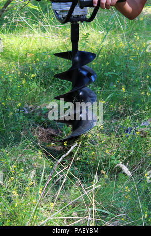 a large spiral drill for drilling holes in ground. reportage shooting. - Stock Photo