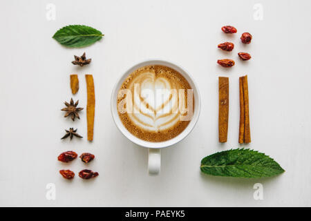 Flat lay a cup of delicious fresh cappuccino on a white surface and various ingredients. - Stock Photo