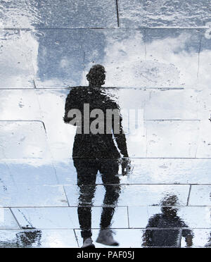 Blurry reflection shadow silhouettes of a young man walking on a rainy patterned city sidewalk - Stock Photo