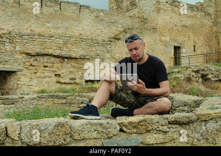 traveler with a tablet on the background of a ruined castle. Search for further directions. Man searching the routes for the further destination while - Stock Photo