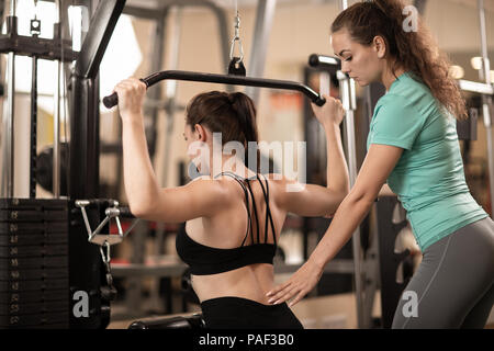 Personal trainer helping girl making excercise in gym - Stock Photo