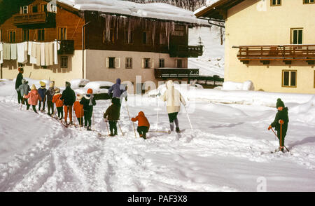 Line of children on skis in ski lesson in Hinterglemm, Austria with small boy looking at camera. Digital conversion of historical photo taken in 1965 - Stock Photo
