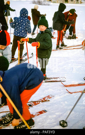 Group of children on old fashioned skis in ski lesson, Hinterglemm, Austria, with small boy looking at camera. Digital conversion of historical photo taken in 1965 - Stock Photo