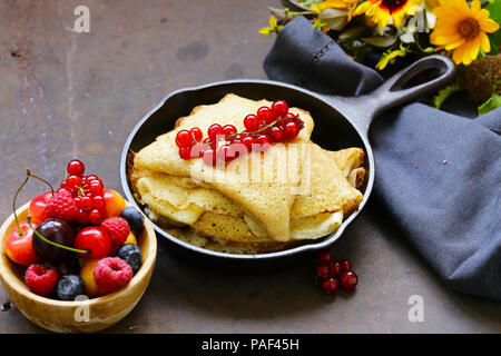 thin pancakes stack in a frying pan, rustic still life - Stock Photo