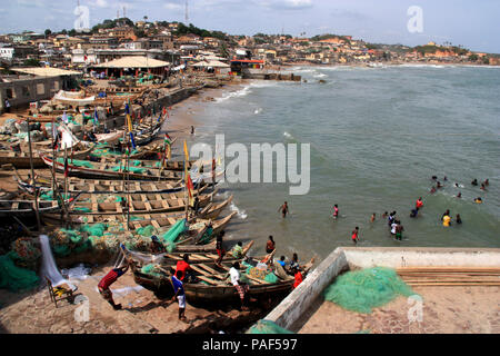 People bathing in the waves of the ocean in front of the stunning cityscape of the slums of Cape Coast, Ghana - Stock Photo