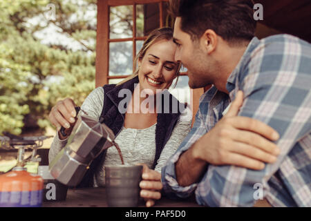 Happy young woman serving coffee to her boyfriend. Couple having coffee in the morning. Woman pouring coffee in the cup of her boyfriend. - Stock Photo