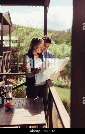 Couple standing in their hotel room balcony and looking at map. Man and woman reading map for finding nearest tourist attraction. - Stock Photo