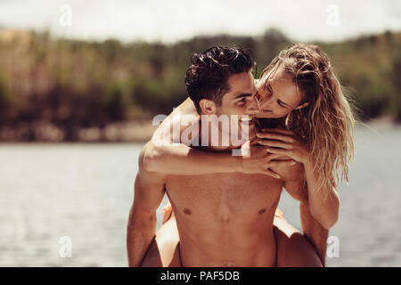 Portrait of romantic young man piggybacking his girlfriend. Young couple having fun at the lakeside. - Stock Photo