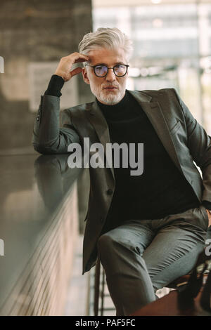 Vertical portrait of handsome mature businessman sitting at cafe counter and looking at camera. Senior man in business suit sitting at coffee shop. - Stock Photo