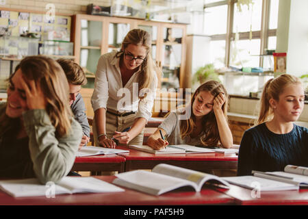Group of university students attending lecture on campus with teacher helping in studies. - Stock Photo