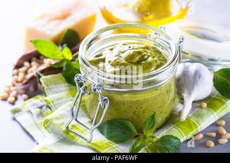 Pesto sauce in glass jar and ingredients.  - Stock Photo
