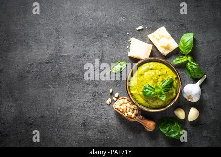 Pesto sauce with ingredients on dark stone table.  - Stock Photo