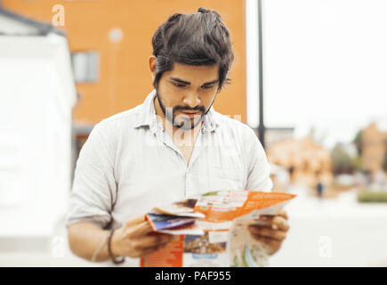 Attractive pensive latin man looking at the map. - Stock Photo