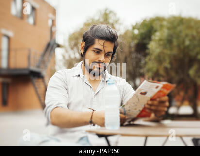 Attractive latin man sitting at street cafe and looking at the map. - Stock Photo