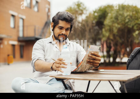 Attractive man sitting at street cafe, looking at the map and holding bottle. - Stock Photo