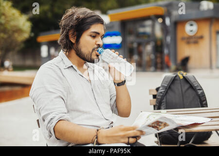 Attractive man sitting at street cafe, looking at the map and drinking water. - Stock Photo