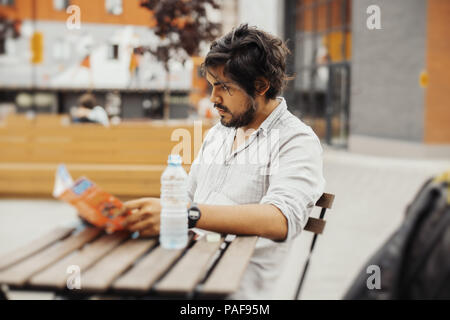 Attractive pensive man sitting at street cafe and looking at the map. Side view - Stock Photo
