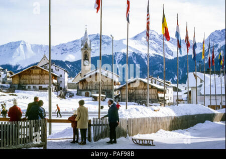1960s Austrian Ski resort with old church and people watching ice skaters on  ice rink in Winter and man pulling wooden sledge. Digital conversion of historical photo taken in ski resort Serfaus, Austria in 1969 - Stock Photo