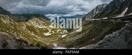Old historic curvy road at the Gotthard mountain pass in Switzerland on a cloudy day with the dramatic sky - Stock Photo