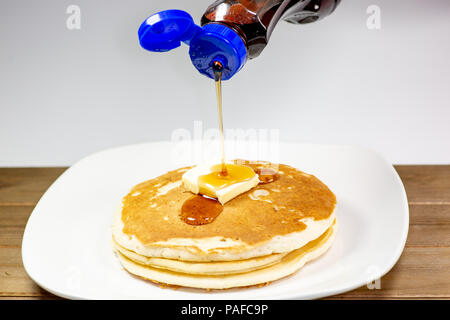 Pouring syrup from a blue tip bottle onto the square of butter on a stack of golden pancakes waiting to be eaten - Stock Photo