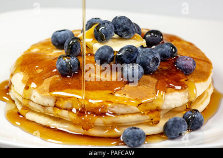 Pouring syrup over the butter on the blueberry stack of pancakes on the kitchen table waiting to be eaten - Stock Photo