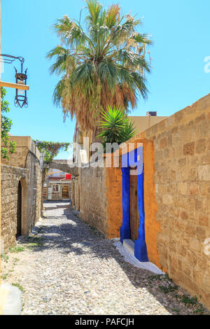 Street view of old town Rhodes, Dodecanese, Greece with yellow and blue entrance - Stock Photo