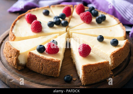 Classic plain New York Cheesecake with fresh berries sliced on wooden board, closeup view, selective focus - Stock Photo