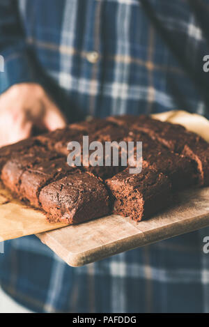 Vegan chocolate brownies with dates and nuts on cutting board. Hands holding tray of freshly baked vegan vegetarian chocolate brownies. Selective focu - Stock Photo