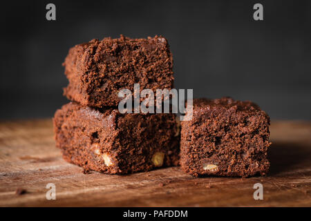 Chocolate brownies with walnuts on wood. Closeup view, selective focus - Stock Photo