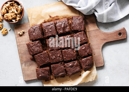 Chocolate brownie squares with walnuts on cutting board, top view, horizontal composition. Flat lay food - Stock Photo