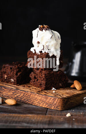 Chocolate brownies with vanilla ice cream on black background. Closeup view, selective focus - Stock Photo