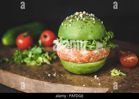 Vegan avocado burger with lentil pattie on wooden cutting board, closeup view. Healthy burger - Stock Photo