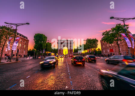 Paris, France - July 2, 2017: Avenue des Champs Elysees and iconic Arc de Triomphe at twilight with traffic street. Arch of Triumph in a colorful sunset sky. - Stock Photo