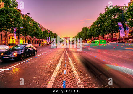 Paris, France - July 2, 2017: speed effect of the cars on the Champs Elysees with the iconic Arc de Triomphe in the distance at twilight. Arch of Triumph in a colorful sunset sky. - Stock Photo