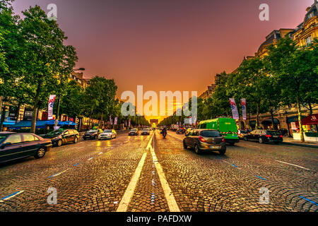 Paris, France - July 2, 2017: perspective view of Champs Elysees with Arc de Triomphe in the distance in a orange sunset sky with road traffic. The arch of Triumph is a famous landmark in Paris. - Stock Photo