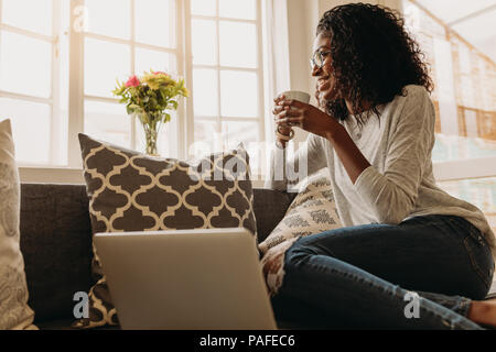 Businesswoman working on laptop computer sitting at home holding a coffee cup in hand. Smiling woman sitting on sofa at home and looking out of the wi - Stock Photo