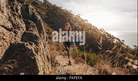 Woman running over extreme terrain on the hillside. Female runner training outdoors on rocky mountain trail. - Stock Photo