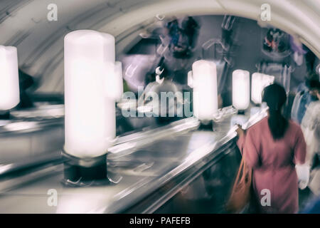 Unrecognizable group of people, girl in red on the escalator in the metro. Blurred abstract background - Stock Photo