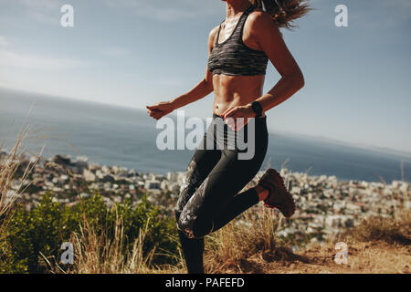 Healthy woman sprinting over mountain trail. Female doing running workout on path over hill. Cropped shot. - Stock Photo