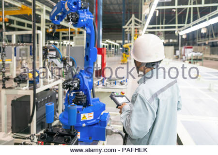 Engineer hand using tablet, heavy automation robot arm machine in smart factory industrial - Stock Photo